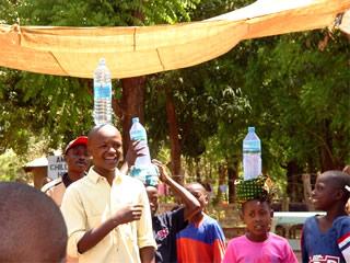 man balancing water bottle on head